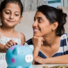 Mother and young daughter putting coins in piggy bank